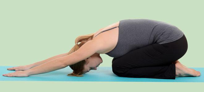 Eine junge Frau macht Yoga um Rückenproblemen vorzubeugen