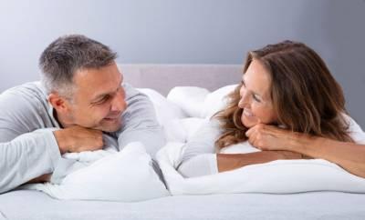 Ein Paar um die 50 liegt im Bett und lächelt sich an.