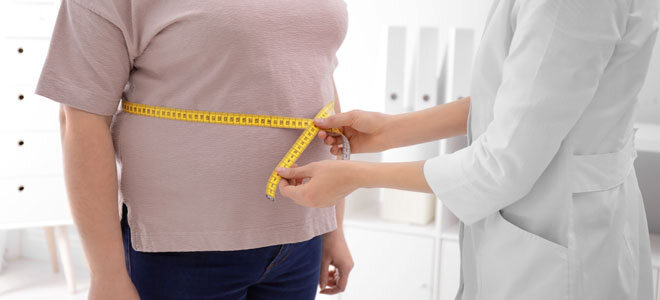 Eine Ärztin misst den Bauchumfang ihrer Patientin.