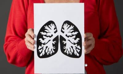 Eine Frau hält ein Schild mit einer Lungengrafik hoch