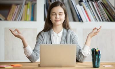 Eine junge Frau meditiert im Büro