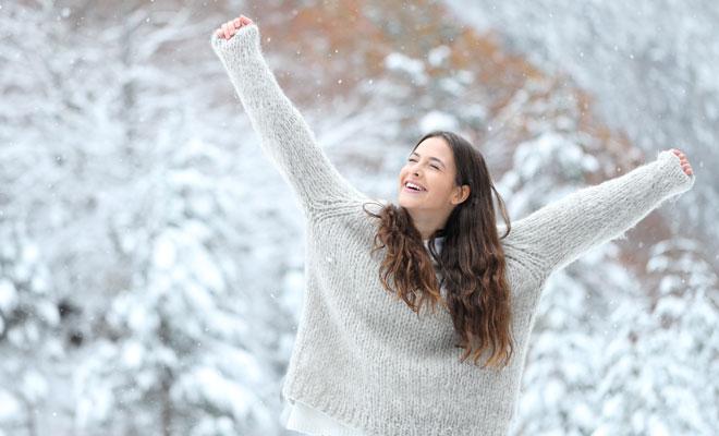 Eine fröhliche junge Frau in einer Winterlandschaft