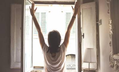 Eine Frau steckt sich vor einem geöffneten Fenster