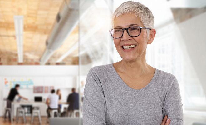 Eine fröhliche Frau um die 50 im Büro