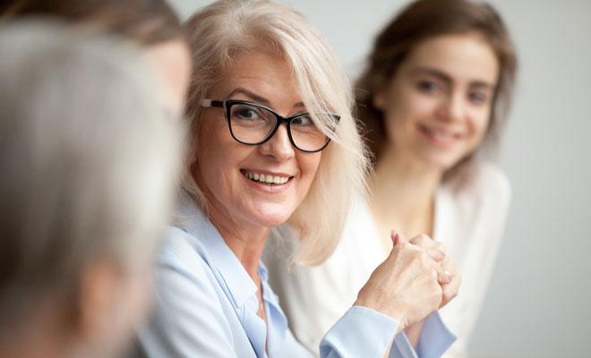 Eine Frau um die 50 spricht mit ihrem Kollegen