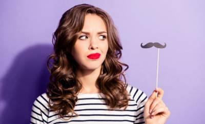 Eine Frau betrachtet einen künstlichen Schnurrbart kritisch. Symbolbild für Damenbart.