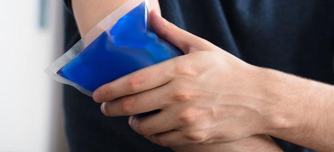 Ein Mann drückt ein Kühlpad auf seinen geprellten Ellbogen
