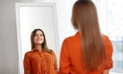 Eine Frau betrachtet ihr Outfit im Spiegel