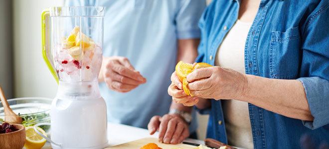 Zwei Senioren mixen einen Smoothie aus frischem Obst.