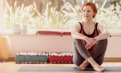 Eine junge Frau praktiziert Yoga, um ihre Menstruationsbeschwerden zu lindern