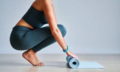 Eine Frau rollt eine Gymnastikmatte auf.