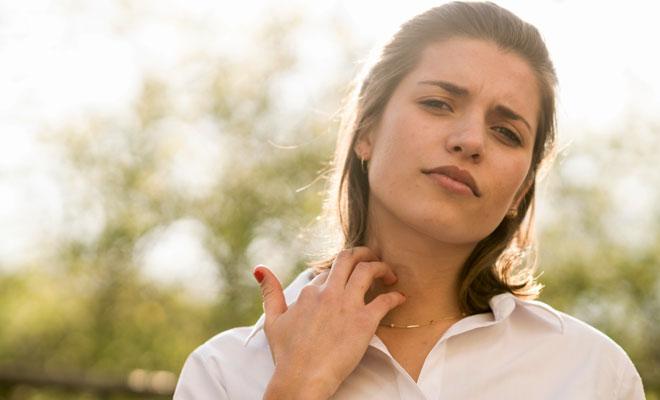 Eine Pollenallergikerin fasst sich an den kratzenden Hals