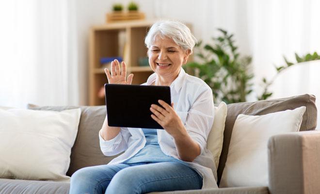 Eine Seniorin chattet per Videoanruf mit ihrer Familie
