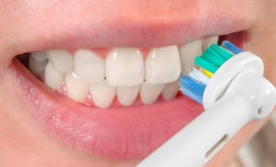 Eine Frau putzt ihre Zähne mit einer elektrischen Zahnbürste