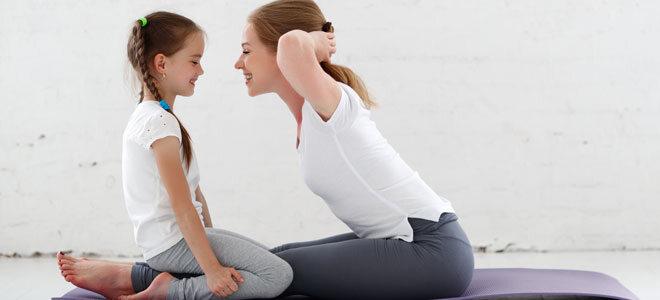 Mutter und Tochter machen zusammen Yoga.