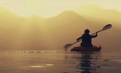 Ein Mann paddelt mit einem Kanu über einen See