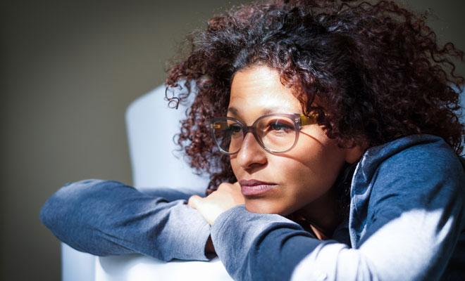 Eine nachdenklich wirkende Frau um die 40