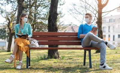 Eine junge Frau und ein junger Mann sitzen zu Coronazeiten mit Abstand auf einer Parkbank