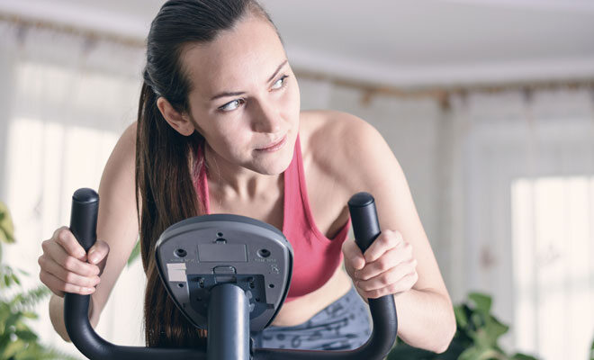 Eine junge Frau trainiert auf einem klappbaren Fahrradtrainer, einem platzsparenden Fitnessgerät