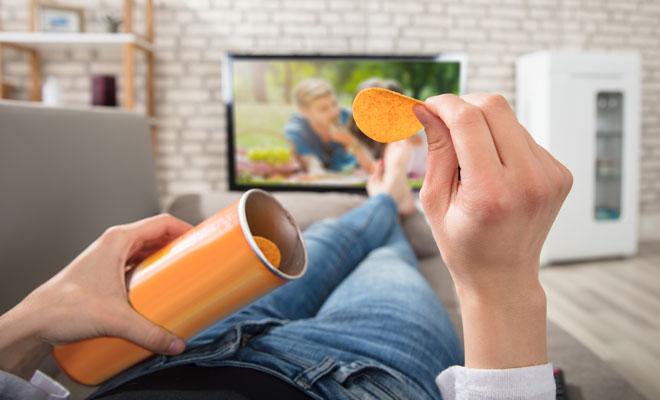 Aus Gewohnheit isst eine Frau Chips beim Fernsehen