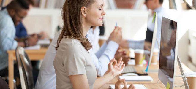 Eine Frau meditiert im Büro
