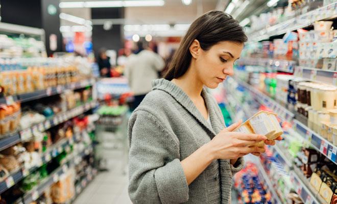 Eine Frau prüft die Zutatenliste auf einem Lebensmittel