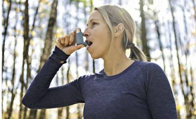 Eine Frau ist von einem Etagenwechsel betroffen und nutzt ein Spray gegen Asthma