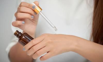 Eine junge Frau trägt ein Hautpflegeöl auf ihre trockenen Hände auf