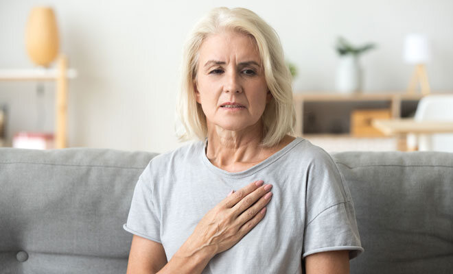Herzinfarkt bei Frauen: Eine Frau verspürt Schmerzen in der Brustregion