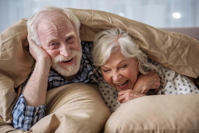 Ein älteres verliebtes Paar lacht zusammen