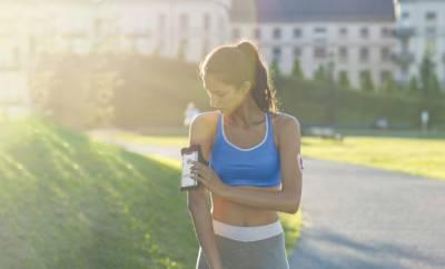 Frau bedient beim Joggen ihr Smartphone am Arm