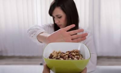Eine Frau lehnt eine Schale mit Nüssen ab, da sie eine Nussallergie hat