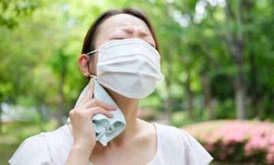 Eine junge Frau schwitzt unter ihrer Mundnasenmaske