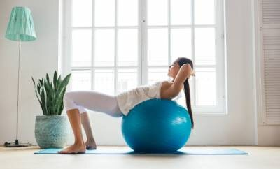 Frau macht Übungen auf einem Gymnastikball