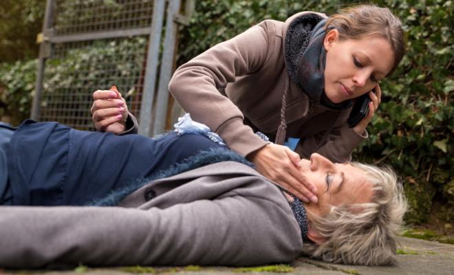 Eine Frau hilft einer bewusstlosen Frau