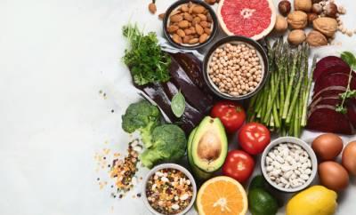 Diverse Gemüse-, Obstsorten, Cerealien und Hülsenfrüchte auf einer weißen Oberfläche, die viel Folsäure enthalten