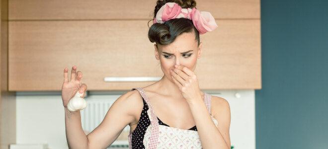 Eine Frau, die eine Knoblauchknolle in der Hand hält, ist angeekelt von dem Geruch und hält sich die Nase zu.