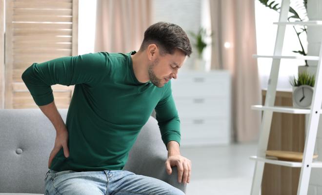Mann sitzt auf dem Sofa und hält sich den unteren Rücken vor Schmerzen