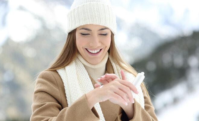 Eine junge Frau cremt sich die Hände ein