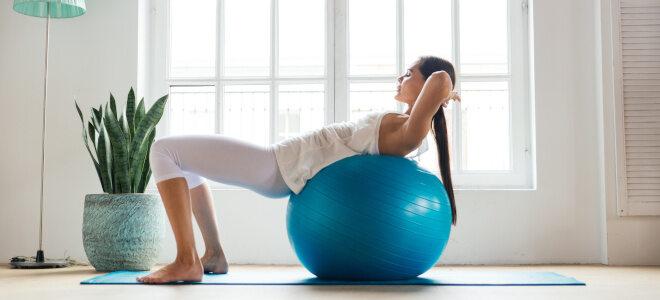 Frau macht Rückenübungen auf einem blauen Gymnastikball