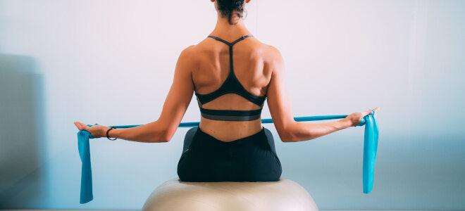 Frau trainiert auf einem Gymnastikball mit einem elastischen Gymnastikband