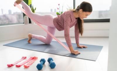 Frau trainiert mit einem Thera-Band auf einer Trainingsmatte. Neben ihr liegen weitere Gymnastikbänder und Hanteln