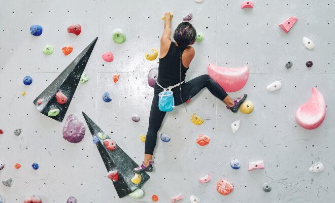 Eine Frau klettert eine Boulderwand hoch