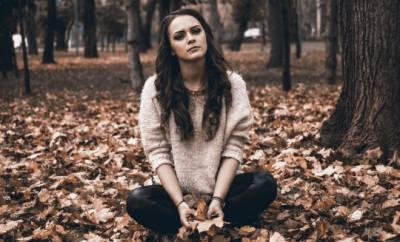 Junge Frau sitzt im Schneidersitz im Herbstlaub