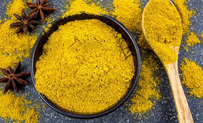 Eine schwarze Schale voll gelbem Currypulver und ein Holzlöffel auf einer dunklen Arbeitsplatte