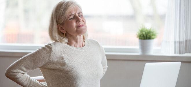 Eine ältere Dame sitzt am Tisch, hat ein schmerzverzerrtes Gesicht und hält sich den Rücken