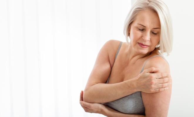 Eine ältere Dame hält sich die rechte Schulter und den linken Ellenbogen