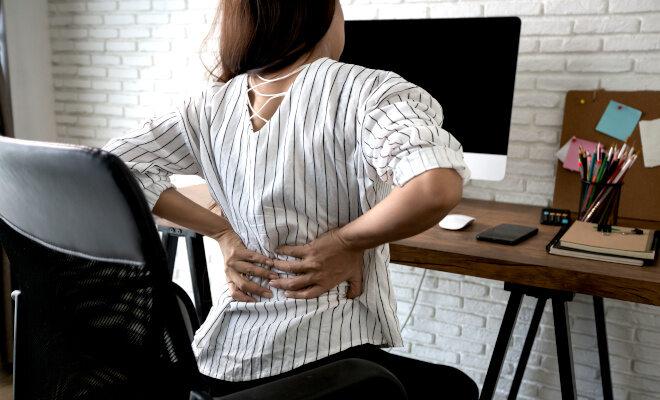 Frau sitzt im Home Office am Schreibtisch und greift sich an den schmerzenden Rücken