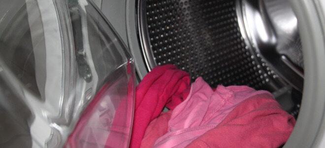 Eine offene Waschmaschine mit rosafarbener Kleidung