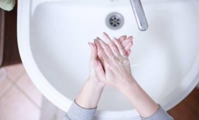 Eine Person wäscht sich in einem weißen Waschbecken die Hände